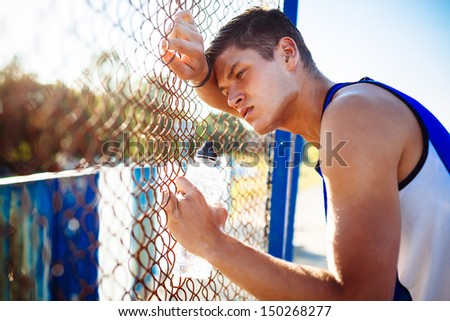 Tired young man resting after workout - stock photo