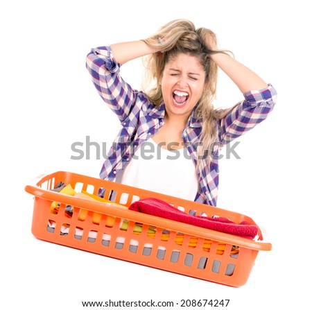 Tired young woman doing the laundry at home - stock photo
