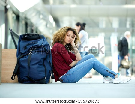 Tired young woman sleeping at airport with luggage - stock photo