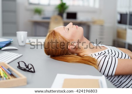 Tired young woman taking a break at work lying back in her chair with her head tilted back on the desk and her eyes closed - stock photo