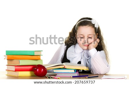 tiredness little girl in black and white uniform sitting  at the table and looking in book, near - many books and red apple, on white background - stock photo