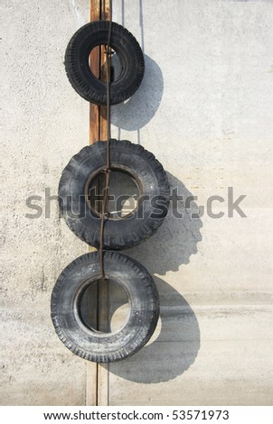 Tires hanging on pier - stock photo