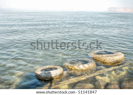 tires in a lake- pollution scenery - stock photo