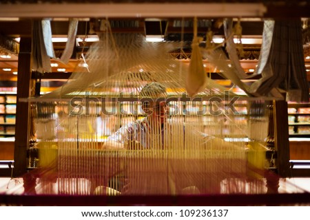 TIRUNELVELI, INDIA - DECEMBER 9: A unidentified Indian man makes a traditional sari to demonstrate a hand loom on December 9, 2009 in Tirunelveli, India. Textile industry is important for India - stock photo