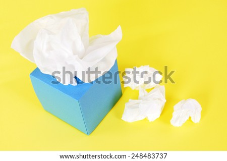 Tissue box :  Kleenex style, used tissues, yellow background. - stock photo
