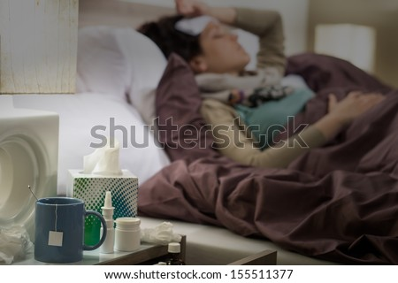 Tissue, flu medicines and tea on bedside table sick woman - stock photo
