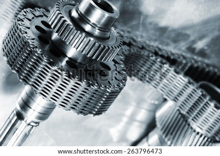 titanium and steel cogs powered by large timing-chain, aerospace engineering parts in blue - stock photo
