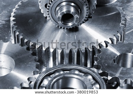 titanium and steel parts, ball-bearings, gears in a blue toning concept - stock photo