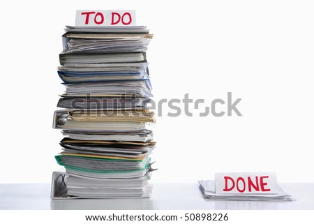 To do and done paperwork in unbalance proportion, against white background - stock photo