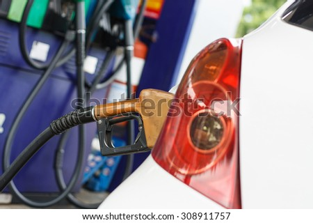To fill the machine with fuel. Car fill with gasoline at a gas station. Gas station pump.Car gas fill up. - stock photo
