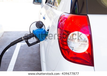 To fill the machine with fuel. Mashunya fill with gasoline at a gas station. Gas station pump. Man filling gasoline fuel in car holding nozzle. Close up. - stock photo