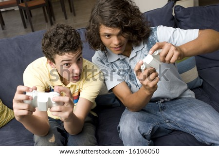 To guys play video games on a couch - stock photo