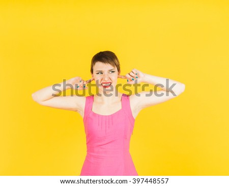 To loud! Young pretty woman in  dress closes her ears with fingers refusing to listen to something.  Isolated portrait with yellow background - stock photo