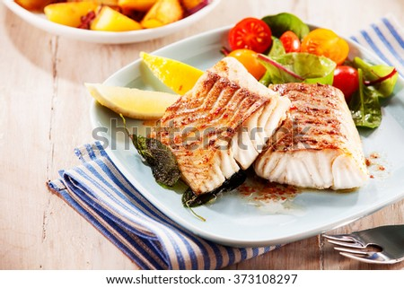 To portions of fresh grilled pollock or coalfish served with colorful salad and slices of lemon, close up high angle view - stock photo