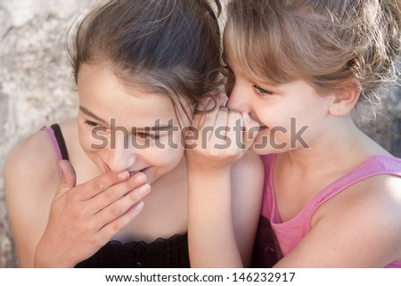 To pretty teenage girls gossiping, giggling and whispering - stock photo