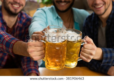 To the weekend! Cropped closeup of three men cheering and toasting with their drinks - stock photo
