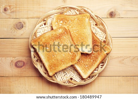 Toast bread in a wicker plate on wooden background. Top view - stock photo