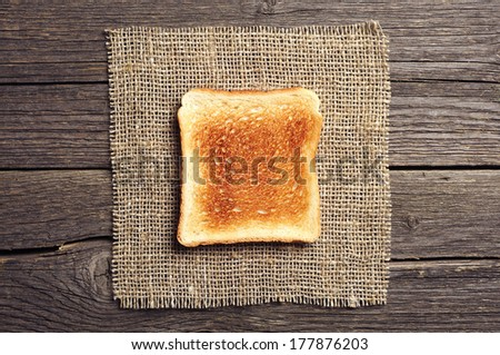 Toast bread on burlap on vintage wooden background. Top view - stock photo