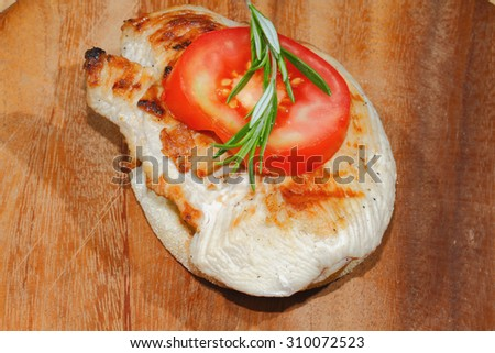 Toast bread with grilled turkey escalope, tomato slices and lettuce, garnished with rosemary - stock photo