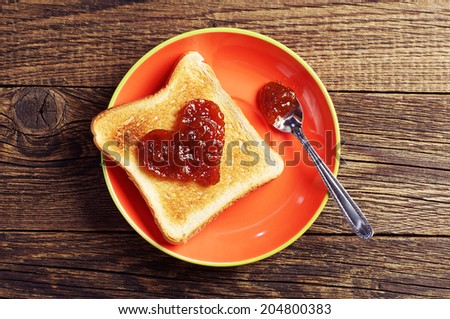 Toast bread with jam in shape of hearts on wooden background. Top view - stock photo
