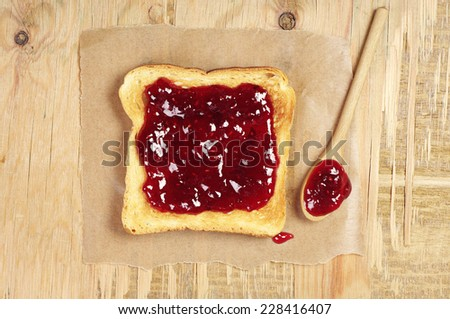 Toast bread with jam on old wooden table. Top view - stock photo