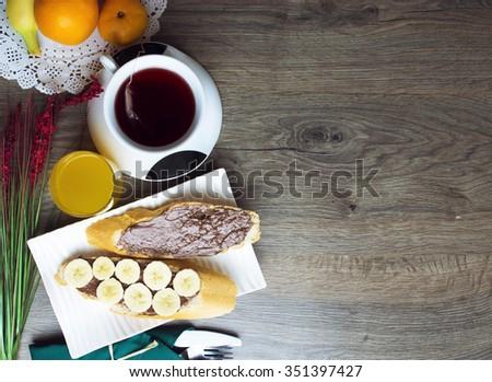 toast, chocolate spread with bread, tea, orange juice, fruit. healthy food, tasty concept. selective focus, toned image - stock photo