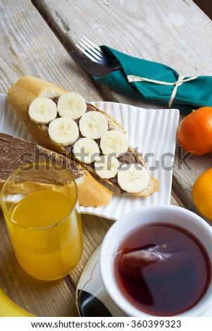 toast, chocolate spread with bread, tea, orange juice, fruit. healthy food, tasty concept. Banana toast. selective focus, toned image - stock photo