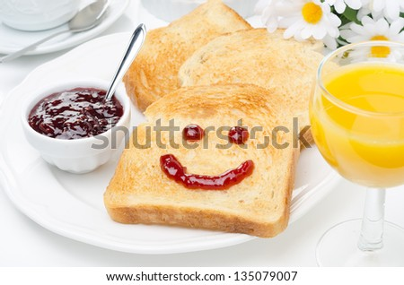 Toast with a smile of jam, coffee, orange juice and fresh oranges for breakfast, horizontal closeup - stock photo
