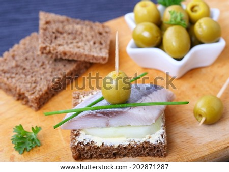 toast with butter,cucumber, olives and salted herring,  selective focus, close up - stock photo
