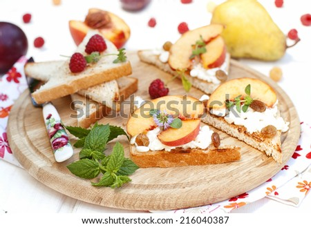 Toast with cottage cheese, raisins and fresh ripe peaches decorated with mint on the wooden surface - stock photo