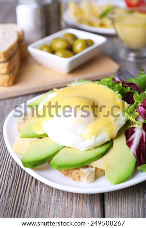 Toast with egg Benedict and avocado on plate on wooden table - stock photo
