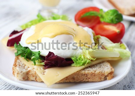 Toast with egg Benedict and tomato on plate on wooden table - stock photo