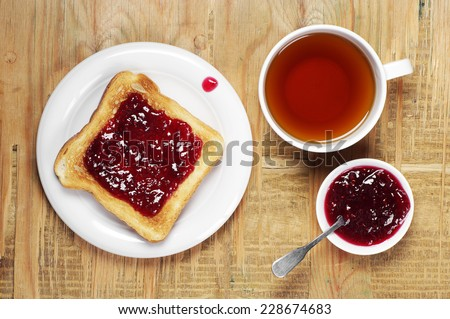 Toast with jam and cup of tea on old wooden table. Top view - stock photo