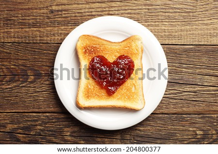 Toast with jam in shape of hearts on wooden background. Top view - stock photo
