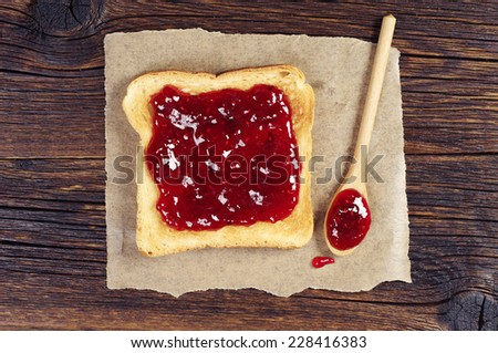 Toast with raspberry jam and spoon on dark wooden table. Top view - stock photo