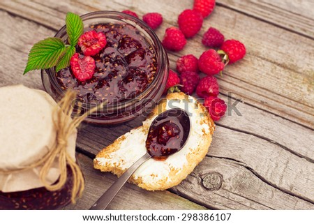 Toast with raspberry jam - homemade marmalade with fresh fruits from garden. All in rustic decoration, Fruit jam on toasted bread. - stock photo