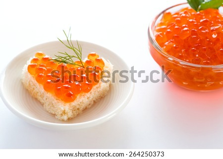 toast with red caviar in heart shape - stock photo