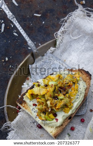 toasted bread snack with basil sauce and zucchini blossoms on rustic background with vintage tray and silver scoop - stock photo
