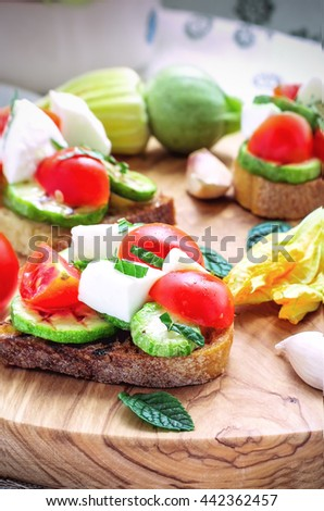 Toasted bread topped with grilled Zucchini, Mozzarella, Cherry Tomatoes, Italian Food, Closeup  - stock photo