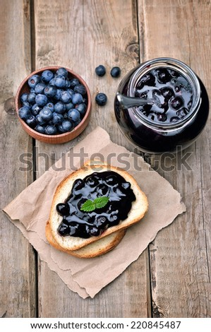 Toasted bread with blueberry jam and jam in glass jar on wooden table, top view - stock photo