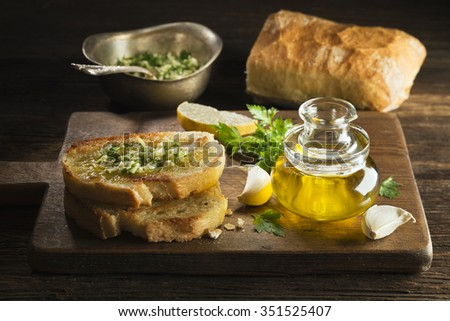 Toasted bread with garlic, herbs and olive oil on wooden background. - stock photo