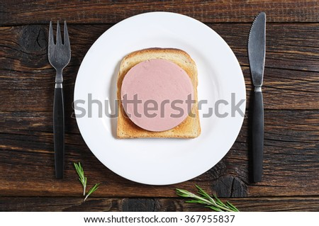 Toasted bread with sausage on old wooden table, top view  - stock photo