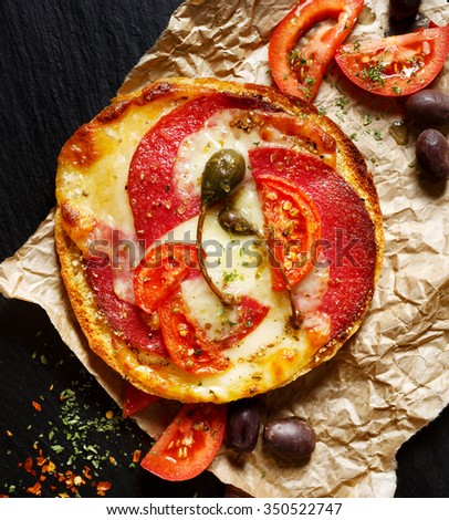 Toasted sandwich with addition of salami, mozzarella cheese, tomatoes and capers - stock photo