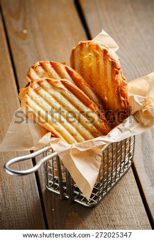 Toasted slices of bread with a golden crust neatly stacked in a metal stand on a wooden brown background - stock photo