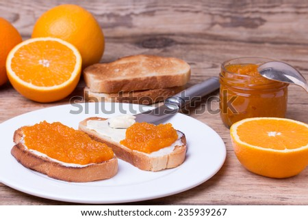 toasted slices of bread with butter and homemade orange jam on white plate. Orange jam in glass jar on rustic wooden board - stock photo