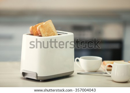 Toaster with dishes on a light kitchen table, close up - stock photo