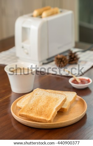 Toaster with sandwiches and jam on a light kitchen table. - stock photo
