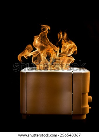 Toaster with two slices of toast caught on fire over black background - stock photo