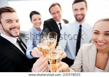 Toasting to success. Group of business people toasting with champagne and smiling while standing close to each - stock photo