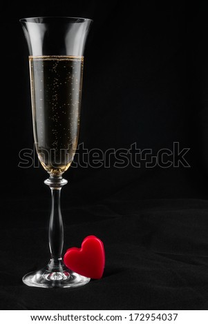 Toasting with champagne and symbolic heart, on a black background  - stock photo